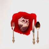 Hjärta och bestick i en blodpöl Arkivbilder