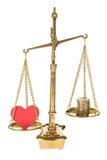 Hjärta och mynt på skala royaltyfria foton