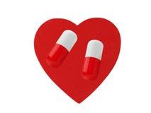 Hjärta och preventivpillerar som isoleras på vit Royaltyfri Bild