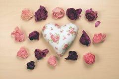 Hjärta och vissnade rosor på pastellfärgad träbakgrund Arkivbilder