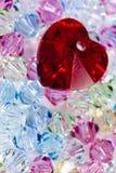 Hjärta på mycket små glass pärlor Arkivfoto