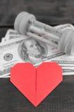 Hjärta, sandglass & sedlar Arkivfoto