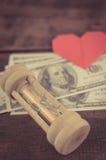 Hjärta, sandglass & sedlar Arkivbilder