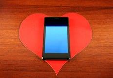 Hjärta Shape och mobiltelefon Arkivbild