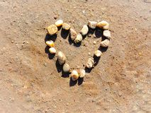 Hjärta Shape som göras från, vaggar kiselstenar i sanden royaltyfri bild