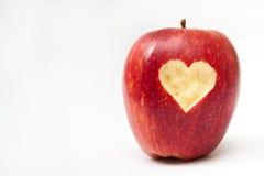 Hjärta sned in i det röda äpplet Arkivfoto