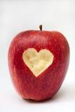 Hjärta sned in i det röda äpplet Arkivbilder