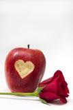 Hjärta sned in i det röda äpplet och röd ros Arkivbild