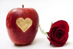 Hjärta sned in i det röda äpplet och röd ros Fotografering för Bildbyråer
