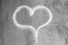 Hjärta som dras i krita på en grå betongvägg arkivfoton