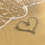 Hjärta som dras i strandsand, försiktig bränningvåg Förälskelse Arkivfoton