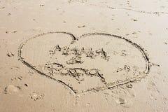 Hjärta som dras på sand i strand med mamma & far inom den Fotografering för Bildbyråer