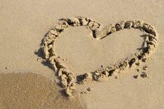 Hjärta som dras på sand och havet, sikt från över arkivfoton