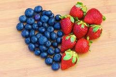 Hjärta som göras av blåbär och jordgubbar Arkivfoton