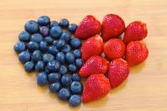 Hjärta som göras av blåbär och jordgubbar Royaltyfri Foto