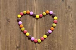 Hjärta som göras av färgrika godisar Arkivbilder