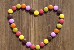 Hjärta som göras av färgrika godisar Arkivbild