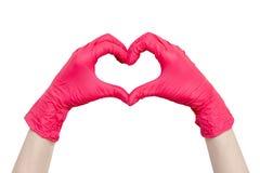 Hjärta som göras av isolerade röda medicinska handskar på vit bakgrund royaltyfria foton