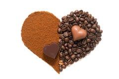 Hjärta som göras av jordkaffe och kaffebönor med chokladhjärtor arkivbild