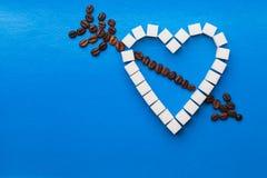 Hjärta som göras av kuber av socker och coffe arkivbild
