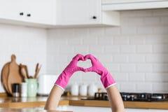 Hjärta som göras av rosa skyddande handskar på vit kökbakgrund Kvinnahänder som bär skyddande handskar Begrepp av arkivbilder