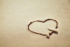 Hjärta som göras av sand på stranden man för begreppskyssförälskelse till kvinnan royaltyfria bilder