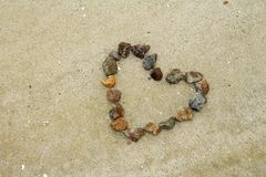Hjärta som göras av stenar på sanden Arkivbilder