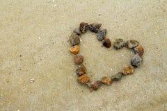 Hjärta som göras av stenar på sanden Arkivbild