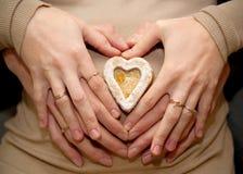 Hjärta som göras med händer på den gravida tummyen, Arkivfoto
