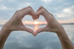 Hjärta som göras med handen och solen, är bakgrunden arkivbilder