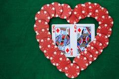 Hjärta som göras med pokerchiper, med konung och drottningen av diamanter, på en grön bakgrundstabell Bästa sikt med kopieringsut arkivbild