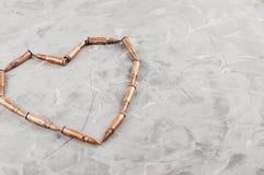 Hjärta som läggas ut ur metallkulor för anfallgevär på grå bruten betong royaltyfria foton
