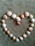 Hjärta som skapas med klämmor av bubblor på strandsand Arkivbild