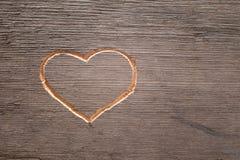 Hjärta som snidas på träplankan royaltyfri bild
