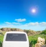Hjärta som tillbaka dras på ett smutsigt fönster i sommartiden Arkivfoto