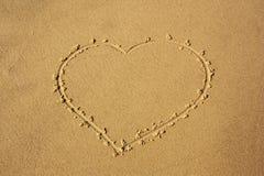 Hjärta som visas på havssand för bakgrund arkivfoton
