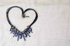 Hjärta till dagen för valentin` s från en härlig, kvinnlig trendig halsband på en svart gummiband med blåa glänsande ädelstenar,  Royaltyfri Foto