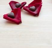 Hjärtachoklad i kronblad på den wood tabellen Royaltyfria Foton