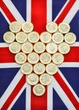 Hjärtaform av nya pundmynt på brittisk flagga Arkivfoto
