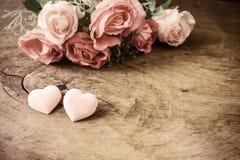 Hjärtaform med rosa färgrosblomman på trätabellen Arkivfoton