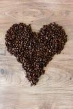 Hjärtaform som överst göras ut ur kaffebönor av en tabell Royaltyfria Foton