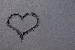 Hjärtaform som dras på den svarta sandstranden arkivbild