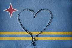 Hjärtaform som drawning på sand med att blanda den Aruba flaggan Royaltyfria Foton