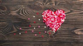 Hjärtaform som göras av små hjärtor på en träbakgrund Fotografering för Bildbyråer