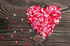 Hjärtaform som göras av små hjärtor på en träbakgrund Arkivfoto