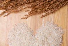 Hjärtaform som göras från korn för vita ris. Arkivfoton