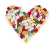 Hjärtaform som göras från medicinkapslar, preventivpillerar och minnestavlor Royaltyfri Bild