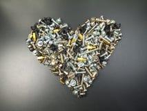 Hjärtaform som göras ut ur blandade skruvar Arkivfoton