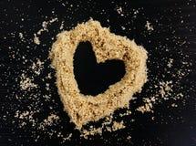 Hjärtaform som göras ut ur strandsand arkivfoto
