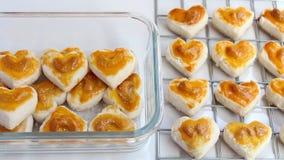 Hjärtaformkakor med kasjun eller den Singapore kakan i den glass bunken på vit tabellbakgrund för begrepp för valentindagbestånds lager videofilmer